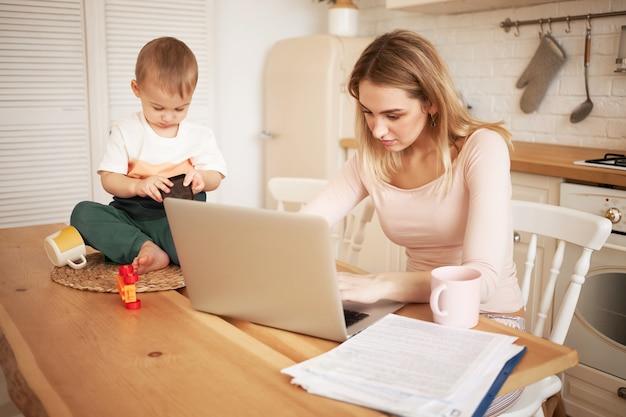 Zmartwiona zdenerwowana młoda blondynka siedząca przy kuchennym stole z papierami i przenośnym komputerem czuje się zestresowana, ponieważ musi złożyć raport i zająć się swoim synkiem, gdy przebywa w domu