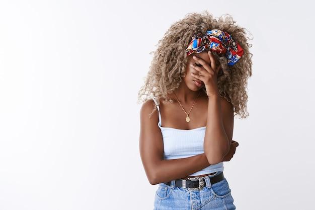 Zmartwiona, zmęczona, przygnębiona stylowa blond dziewczyna z kręconymi włosami w opasce, topu, facepalm, zamknięte oczy zakrywają twarz dłonią ze zmęczenia, zirytowana i rozczarowana, biała ściana