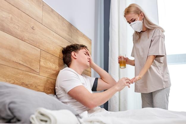 Zmartwiona żona opiekuje się chorym mężem, gdy siedzi na łóżku w domu i podaje leki, ludzie muszą nosić maski medyczne chroniące przed pandemią koronawirusa covid-19, poddane kwarantannie