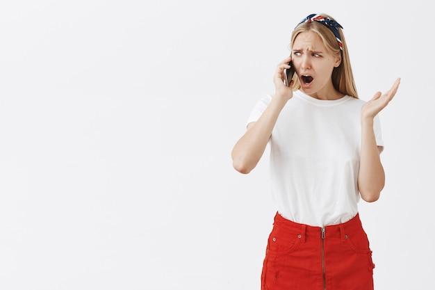 Zmartwiona zszokowana młoda blond dziewczyna pozująca pod białą ścianą