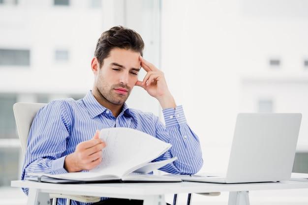 Zmartwiony biznesmen patrzeje dzienniczek