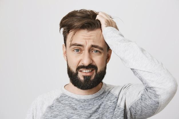 Zmartwiony brodaty facet w panice wyrzucający włosy i wyglądający na przestraszonego