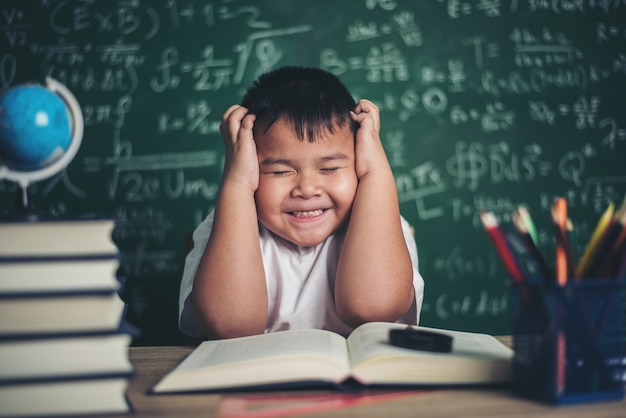 Zmartwiony chłopiec w klasie z rękami na głowie