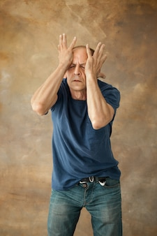 Zmartwiony dojrzały mężczyzna dotykający głowy i myślący dalej.