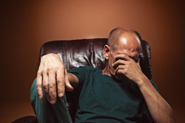 Zmartwiony dojrzały mężczyzna siedzi