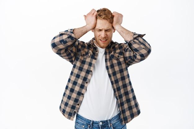 Zmartwiony dorosły rudy mężczyzna ma ból głowy, trzyma ręce na głowie i wygląda na zdenerwowanego, rozczarowanego lub sfrustrowanego porażką, stojąc nad białą ścianą