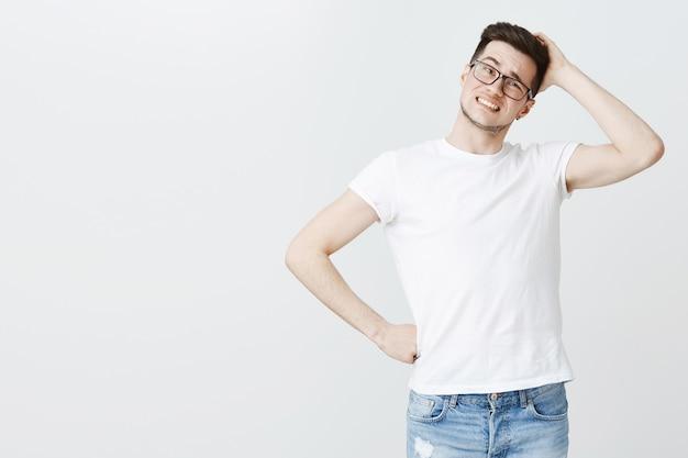 Zmartwiony facet w okularach drapiąc się po głowie niepewnie, myśląc