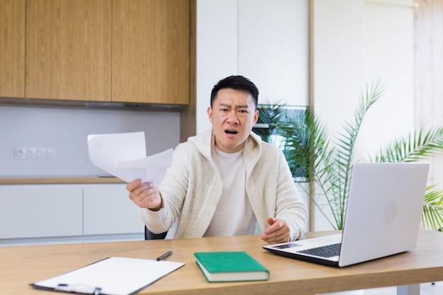 Zmartwiony i zestresowany mężczyzna oblicza rachunki, wydatki podatkowe i liczy domowe finanse