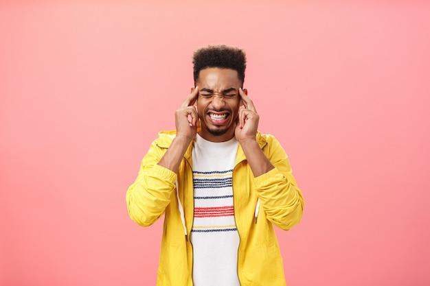 Zmartwiony, intensywny afroamerykanin nie radzi sobie z naciskiem zaciskania zębów, zamykając oczy, trzymając palce na skroniach, nie może się skoncentrować będąc pod wpływem stresu, czując ból głowy lub migrenę na różowym tle.