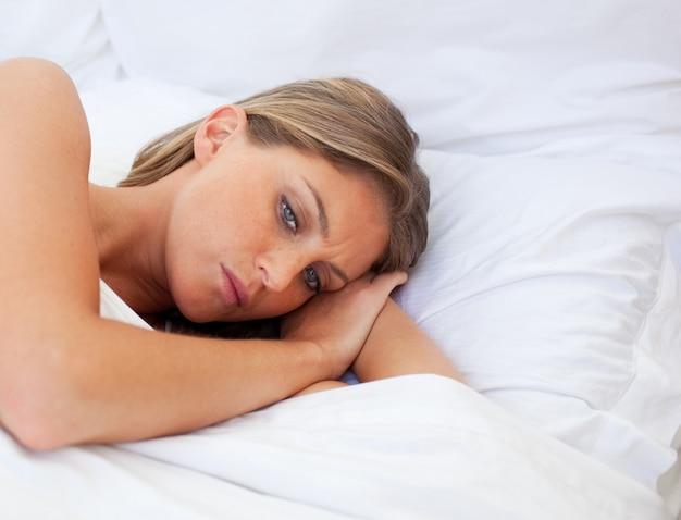 Zmartwiony kobiety lying on the beach na jej łóżku