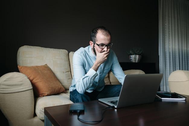 Zmartwiony mężczyzna czyta wiadomości na laptopie, pracując zdalnie ze swojego salonu w domu