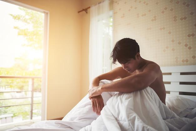 Zmartwiony mężczyzna obsiadanie na łóżku w ranku, poważny główkowanie coś