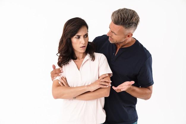 Zmartwiony mężczyzna próbuje pocieszyć swoją dziewczynę, stojąc na białym tle nad białą ścianą