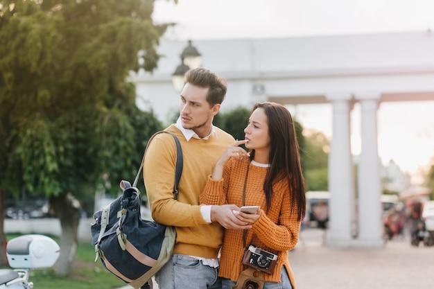 Zmartwiony mężczyzna z plecakiem odwracając wzrok, stojący obok pięknej kobiety w pomarańczowych ubraniach