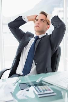 Zmartwiony młody biznesmen przy biurowym biurkiem