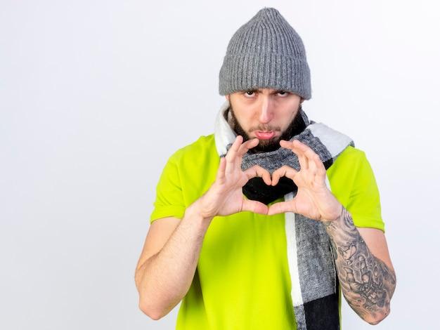 Zmartwiony młody chory człowiek ubrany w czapkę zimową i szalik, wskazując ręką znak serca na białym tle na białej ścianie