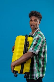 Zmartwiony młody człowiek afroamerykański podróżnik trzyma walizkę