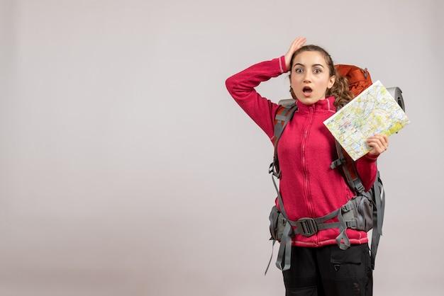 Zmartwiony młody podróżnik z dużym plecakiem trzymającym mapę