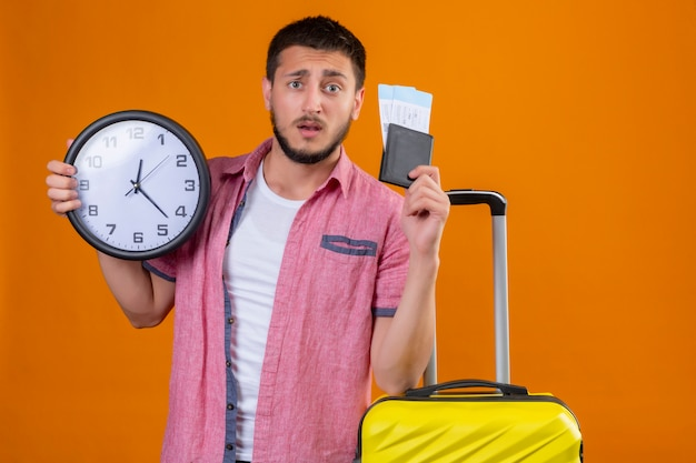 Zmartwiony młody przystojny podróżnik trzymający bilety lotnicze i zegar patrząc na kamerę z zmieszanym wyrazem twarzy stojącej z walizką na pomarańczowym tle