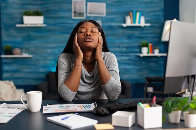 Zmartwiony niezadowolony afrykański student cierpiący na migrenę głowy siedzący przy biurku w salonie ...