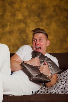 Zmartwiony przestraszony modny mężczyzna w białym ubraniu przytula poduszkę i odwraca wzrok. emocjonalny słodki młody chłopak dostaje okropne wieści lub ogląda horror. pojęcie strachu. przestrzeń praw autorskich