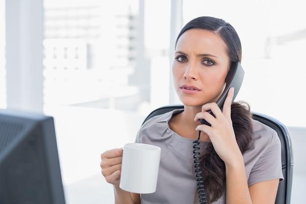 Zmartwiony sekretarz odpowiadając na telefon