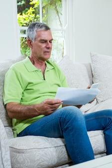 Zmartwiony starszy mężczyzna trzyma dokumenty w domu