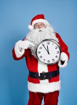 Zmartwiony święty mikołaj trzyma zegar