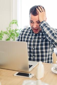 Zmartwiony wstrząśnięty mężczyzna patrząc na laptopa w kawiarni