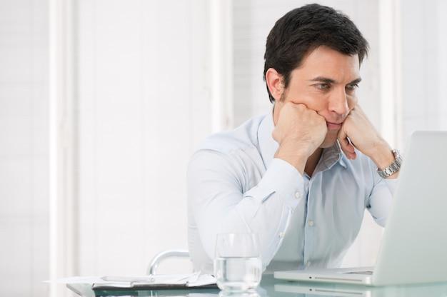 Zmartwiony zamyślony biznesmen ogląda na swoim laptopie w biurze