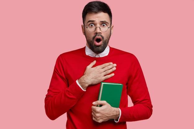 Zmartwiony, zdumiony kaukaski mężczyzna z przestraszonym wyglądem, trzyma rękę na piersi, trzyma zielony zeszyt, nosi czerwony sweter