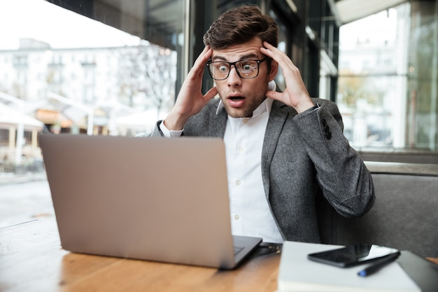 Zmartwiony zmieszany biznesmen siedzi przy stołem w kawiarni w okularach podczas gdy trzymający głowę i patrzejący laptop