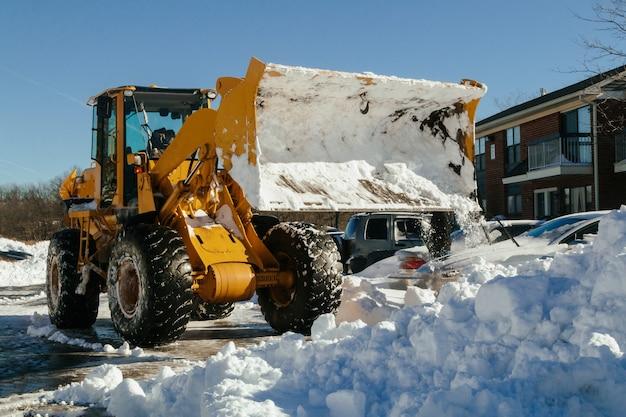 Zmechanizowany ciągnik do odśnieżania zaparkowany jest na ulicy miasta po sezonie zimowym z opadami śniegu