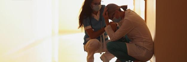 Zmęczeni lekarze w ochronnej masce medycznej siedzą na korytarzu