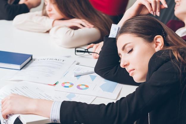 Zmęczeni menedżerowie korporacji. koncepcja przepracowania. członkowie zespołu firmy spanie na biurku.