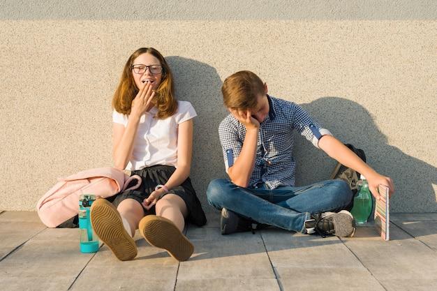 Zmęczeni nastolatkowie w wieku szkolnym siedzą na zewnątrz przy szarej ścianie z książkami, plecakami