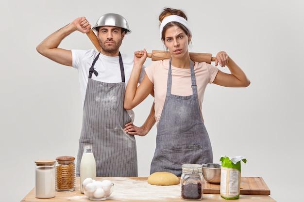 Zmęczeni szefowie kuchni noszą fartuchy, trzymają wałki do ciasta za plecami, robią sobie przerwę po przygotowaniu ciasta, zajęci planowaniem menu, pozują w kuchni. kulinarni partnerzy wspólnie przygotowują domowe ciasto na specjalne okazje