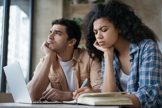 Zmęczeni zamyśleni studenci studiujący razem przygotowujący do egzaminu