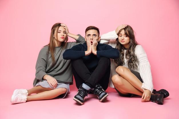 Zmęczeni znudzeni młodzi przyjaciele siedzi na różowej podłoga