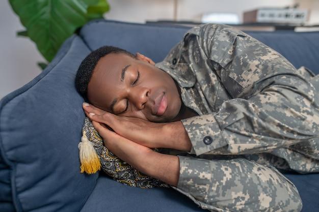 Zmęczenie, sen. młody dorosły afroamerykanin w wojskowym mundurze śpi na kanapie z rękami pod głową w domu