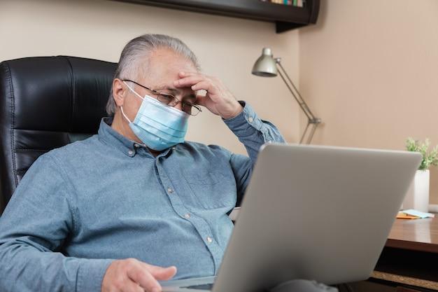 Zmęczenie starszy mężczyzna w masce na twarzy pracuje lub komunikuje się na laptopie w domu. nauka, szkolenia, praca, komunikacja, rozrywka, wypoczynek w okresie koronawirusa.