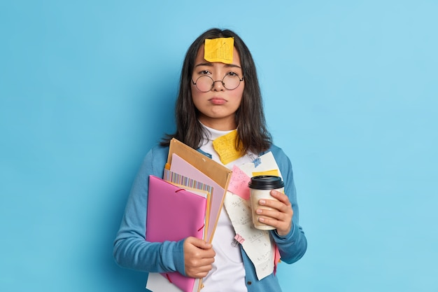 Zmęczenie zestresowana studentka zajęta przygotowywaniem raportu lub pracą na papierze dyplomowym pije kawę, aby odświeżyć ma naklejkę z grafiką na czole zmęczoną pracą.
