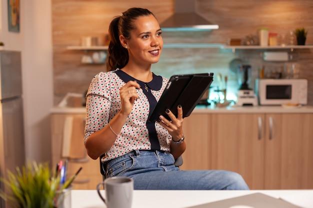 Zmęczona, ale szczęśliwa kobieta korzystająca z komputera typu tablet o północy, aby zakończyć projekt do pracy. pracownik korzystający z nowoczesnych technologii o północy wykonujący nadgodziny w pracy, biznesie, karierze, sieci, stylu życia, bezprzewodowo.