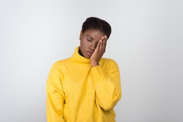 Zmęczona amerykanin afrykańskiego pochodzenia kobieta trzyma rękę na twarzy
