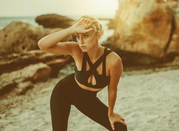 Zmęczona atrakcyjna kobieta fitness w odzieży sportowej na dzikiej plaży.