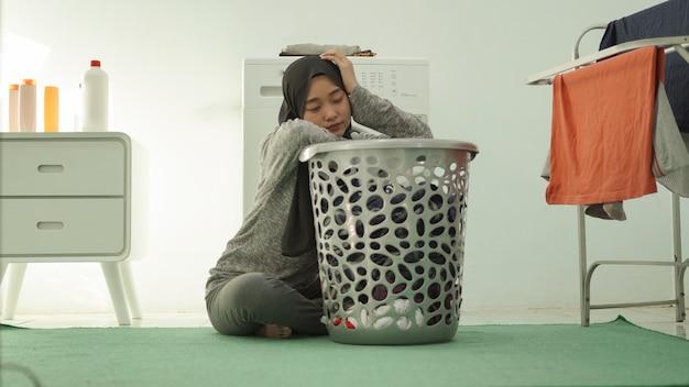 Zmęczona azjatycka kobieta w hidżabie piorąca ubrania w domu