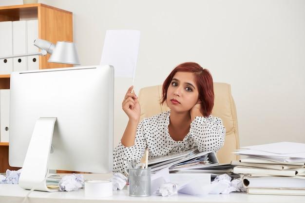Zmęczona beznadziejna ładna młoda bizneswoman oparta na stosie dokumentów i podnosząca rękę z białymi ...