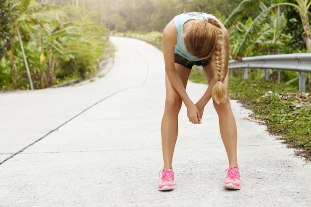 Zmęczona biegaczka odpoczywająca po ciężkim biegu po leśnej drodze, pochylająca się do przodu, opierając łokcie na kolanach.