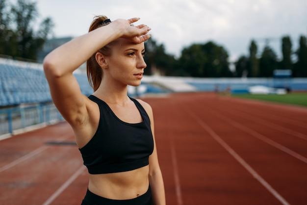 Zmęczona biegaczka w odzieży sportowej, trening na stadionie. kobieta robi ćwiczenia rozciągające przed bieganiem na arenie na świeżym powietrzu