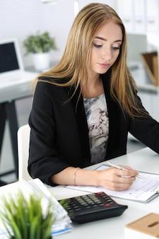 Zmęczona biznesowa kobieta pracuje w biurze. pojęcie stresu i nadgodzin